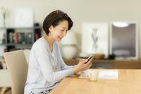 スマホを操作する日本人のシニア女性