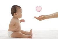 お座りしている赤ちゃんとハートが乗ってるママの手