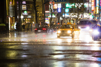 濡れた地面に反射した車のライト