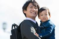 息子を抱きかかえる父親