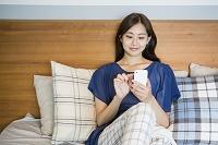 ベッドでスマートフォンを使う20代日本人女性