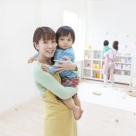 日本人の子供を抱く保育士