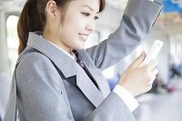 電車の中でスマートフォンを持つ女子高生