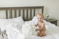 ベッドで遊ぶ外国人の赤ちゃん