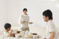 ダイニングテーブルにおかずを運ぶママと食事をとる日本人親子