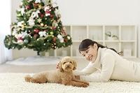 クリスマスツリーのあるリビングでくつろぐ女性と犬