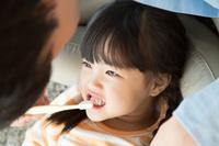 女の子の歯磨きをしてあげる父親