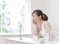 鏡を見てスキンケアをする日本人女性