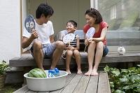 縁側に座った家族と桶のスイカとジュース
