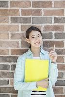 ファイルを持って指差しをする20代日本人女性