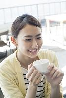 カフェテラスでカップを持って微笑む20代日本人女性