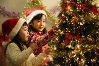 クリスマスツリーの飾りつけをする日本人の女の子