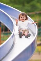 公園の滑り台で遊ぶ女の子