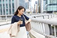 コーヒーを持って通勤する日本人女性