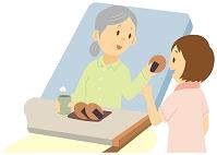 ベッドでおやつを食べる老人女性と介護士