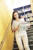 本を運びながら階段を下りる女子大学生