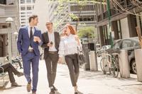同僚と話ながら街中を歩くビジネスマン