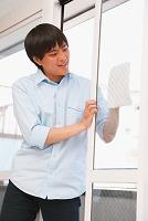 ガラスを拭く若い日本人男性
