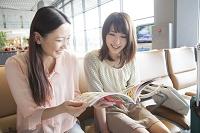 空港で旅行雑誌を見る日本人女性達