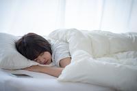 ベッドで眠る若い女性