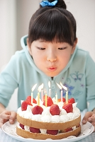 バースデーケーキの火をふく日本人の女の子