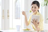 タブレットを見ながら朝食を食べる日本人女性