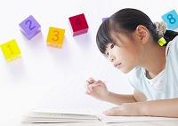 勉強する小学生の女の子と数字のブロック