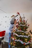 クリスマスツリーを飾る親子