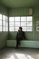 駅の待合室で電車の待つ日本人男性