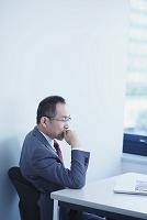 真剣にモニタを見つめるシニア日本人ビジネスマン