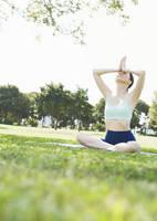 公園でヨガをする若い女性