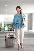旅行かばんを持って歩く中高年日本人女性