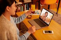 パソコンで友達とオンライン飲み会を楽しむ若者