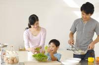 料理をするパパとママを手伝う男の子