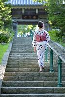 階段を上がる浴衣の女性の後ろ姿