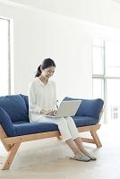 ソファーでパソコンを使う20代日本人女性