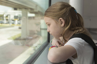 窓辺から遠くを見る女の子