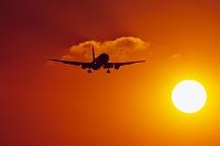 着陸するボーイング767と夕日
