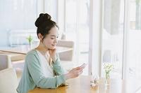 カフェでスマートフォンを見る日本人女性