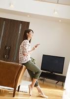 ソファに寄り掛かってスマートフォンを操作する日本人女性