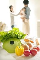 キッチンに置かれた野菜と赤ちゃんを抱く両親