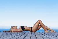 仰向けで横たわる水着姿の女性