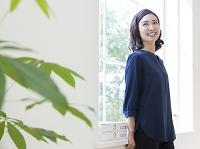 窓辺に立つ40代の日本人女性