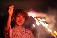 花火を掲げる浴衣姿の若い女性