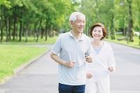 新緑とジョギングをするシニア夫婦