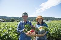 畑で収穫した野菜を見せる中高年夫婦