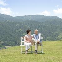 草原でベンチに座る中高年夫婦