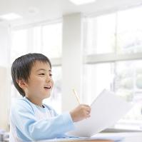 教室で勉強する笑顔の日本人の男の子