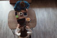 パソコンとタブレットを見ながら朝食をとる外国人カップル