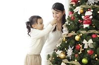 クリスマスツリーの飾りつけをする親子